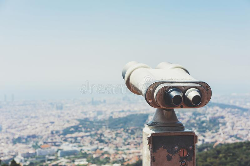 Touristic telescope look at the city with view of Barcelona Spain, close up old metal binoculars on background viewpoint overlook. Ing the mountain, hipster coin royalty free stock photography