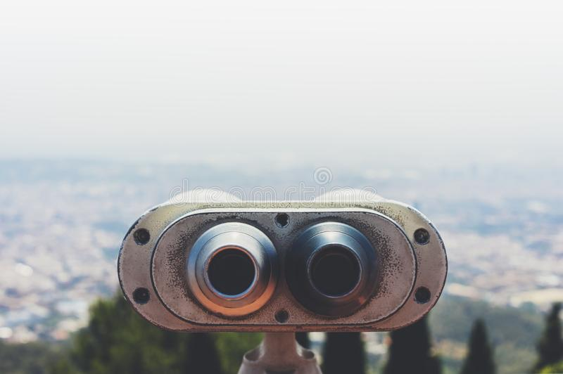 Touristic telescope look at the city with view of Barcelona Spain, close up old metal binoculars on background viewpoint overlook. Ing the mountain, hipster coin stock photo