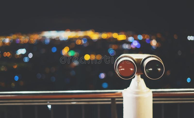 Touristic telescope look at city with view of Barcelona Spain, close up old metal binoculars on background viewpoint, hipster coin. Operated in panorama stock photo
