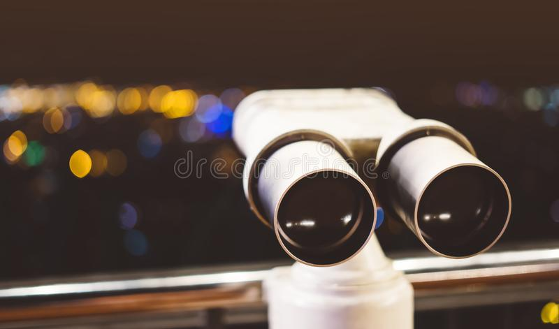 Touristic telescope look at city with view of Barcelona Spain, close up old metal binoculars on background viewpoint, hipster coin. Operated in panorama stock photography