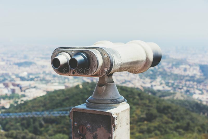 Touristic telescope look at the city with view of Barcelona Spain, close up old metal binoculars on background viewpoint overlook. Ing the mountain, hipster coin stock images