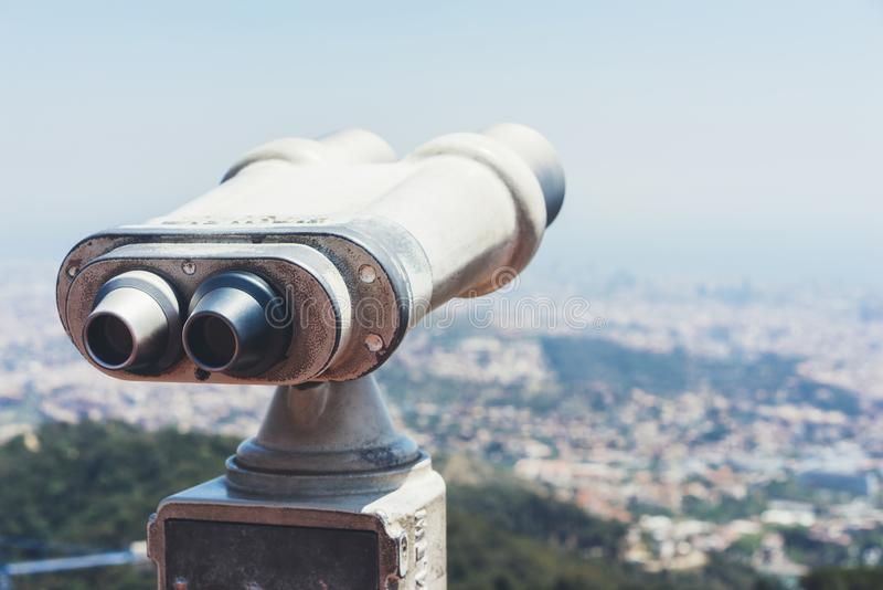 Touristic telescope look at the city with view of Barcelona Spain, close up old metal binoculars on background viewpoint overlook. Ing the mountain, hipster coin stock photography