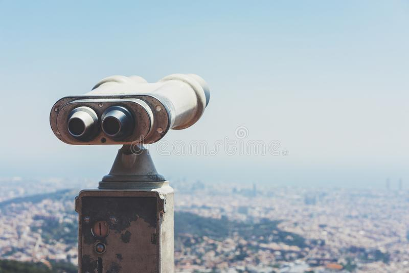 Touristic telescope look at the city with view of Barcelona Spain, close up old metal binoculars on background viewpoint overlook. Ing the mountain, hipster coin stock image