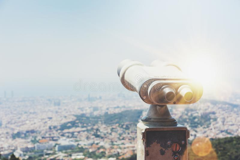 Touristic telescope look at the city with view of Barcelona Spain, close up old metal binoculars on background viewpoint overlook. Ing the mountain, hipster coin royalty free stock photo
