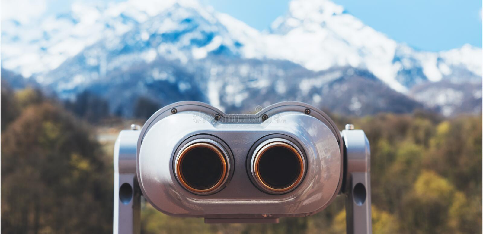 Touristic telescope look at the city with view snow mountains, closeup binocular on background viewpoint observe vision, metal. Coin operated in panorama stock image