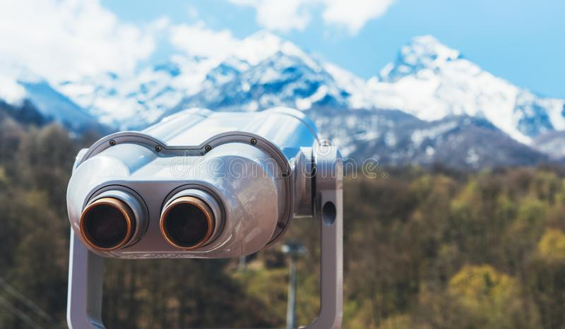 Touristic telescope look at the city with view snow mountains, closeup binocular on background viewpoint observe vision, metal. Coin operated in panorama royalty free stock photo