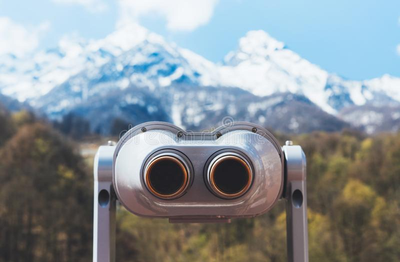 Touristic telescope look at the city with view snow mountains, closeup binocular on background viewpoint observe vision. Metal coin operated in panorama royalty free stock photography