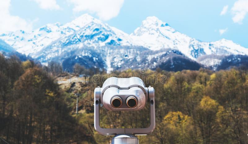 Touristic telescope look at the city with view snow mountains, closeup metal binocular on background viewpoint observe vision. Coin operated in panorama royalty free stock image