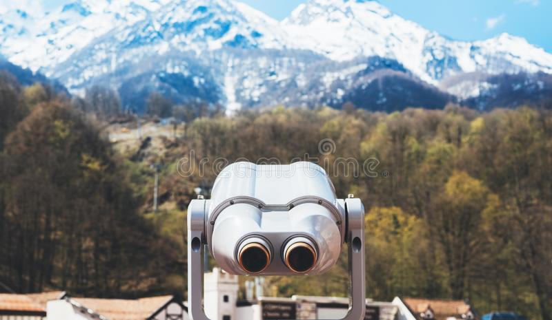 Touristic telescope look at the city with view snow mountains, metal binocular on background viewpoint observe vision, closeup. Coin operated in panorama stock image