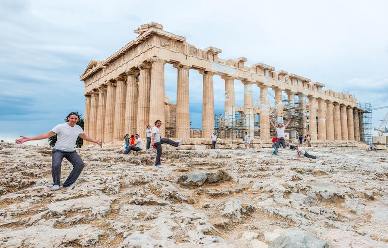 Touristisch in der Mehrfachbelichtung, die in den verschiedenen Haltungen vor dem berühmten Parthenon auf Akropolishügel aufwirft stockfotografie