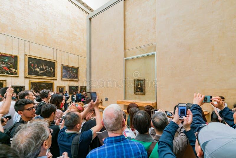 Touristisch, die berühmte Mona Lisa-Malerei im Louvre-Museum in Paris fotografierend lizenzfreie stockfotografie