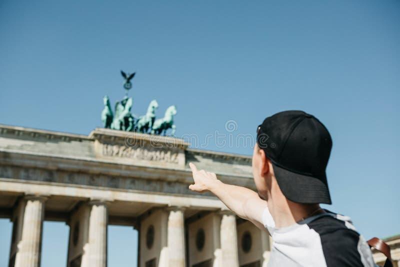 Touristisch oder Kerl zeigt seine Hand auf dem Brandenburger Tor in Berlin lizenzfreies stockfoto