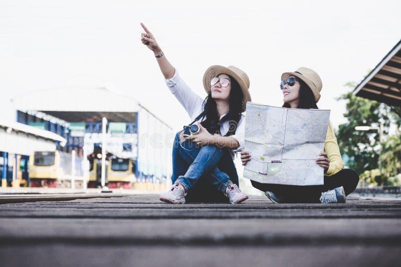 Touristische asiatische Lebensstilfreundfrauen, die den Rucksack hält Karte tragen, Reisenden, der für die Aufwartung eines Zugs  lizenzfreies stockfoto