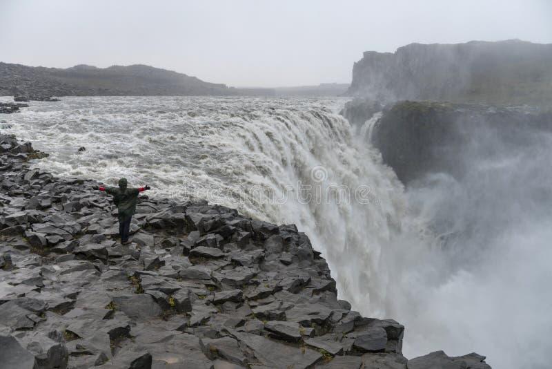 Touristische bewundern Ansicht des fallenden Wassers des stärksten Wasserfalls in Europa - Dettifoss stockfotos