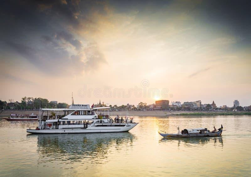 Touristische Boote auf Sonnenuntergang kreuzen in Fluss Phnom Penh Kambodscha lizenzfreies stockfoto