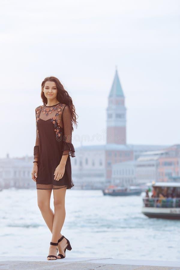 Touristische Frau der Reise auf Pier gegen schöne Ansicht über venetianisches chanal in Venedig, Italien lizenzfreie stockfotos