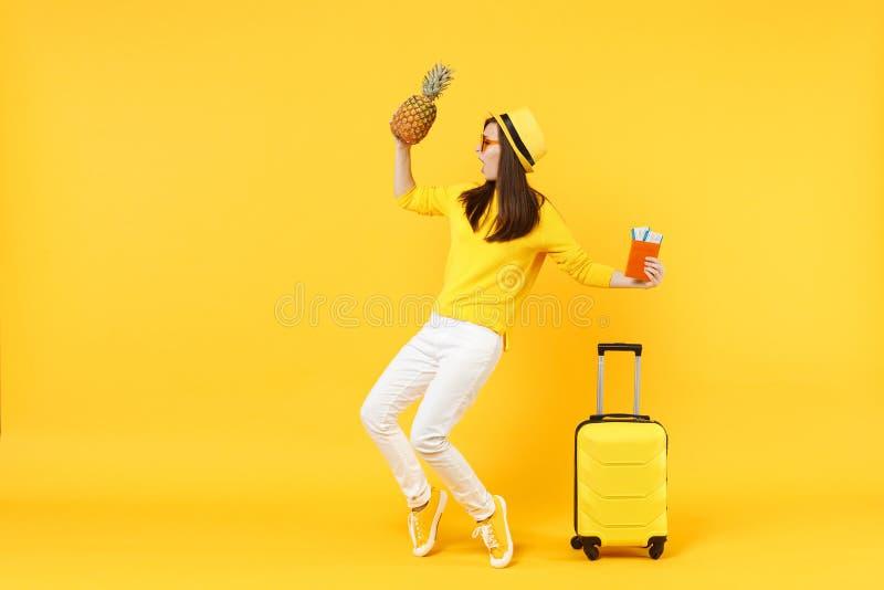 Touristische Frau des Tanzenreisenden in den Hutholding-Passkarten, frische Ananasfrucht lokalisiert auf gelb-orangeem stockfotografie