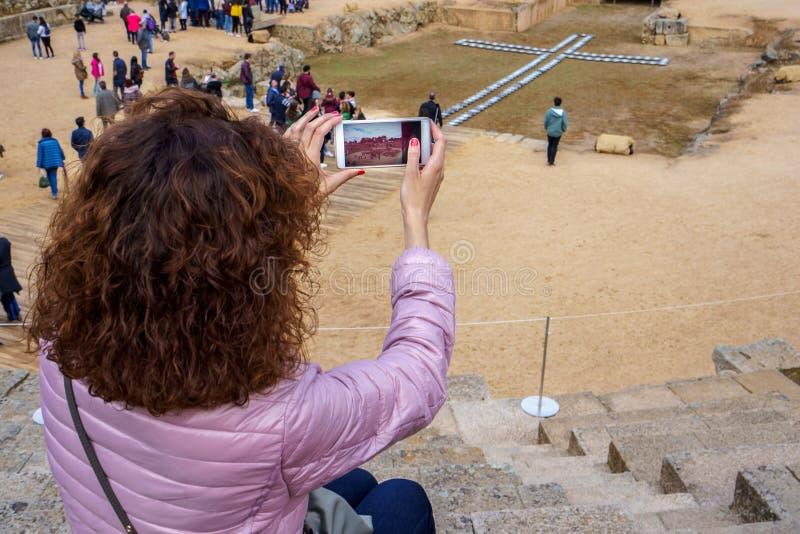 Touristische Frau, die ein Foto mit einem Smartphone von Roman Amphitheatre von Mérida macht stockfotografie