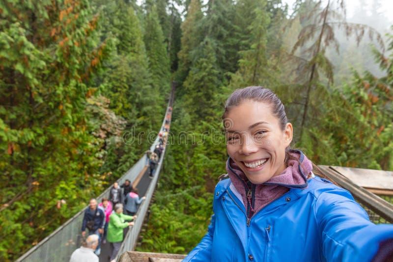 Touristische Frau Kanada-Reise, die selfie Foto an Capilano-Hängebrücke in Vancouver, Britisch-Columbia macht lizenzfreie stockfotografie