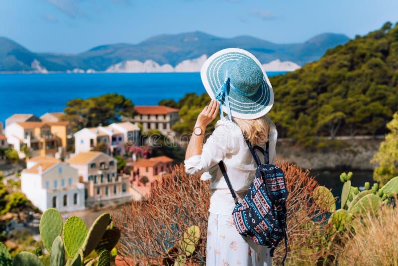 Touristische Frau mit blauem sunhat, weiße Kleidung und Reiserucksack bewundern Ansicht des bunten ruhigen Dorfs Assos an lizenzfreies stockfoto