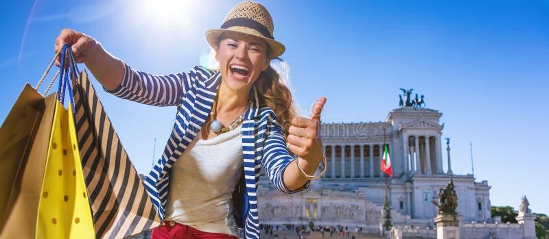 Touristische Frau mit Einkaufstaschen in Rom, das sich Daumen zeigt stockbild