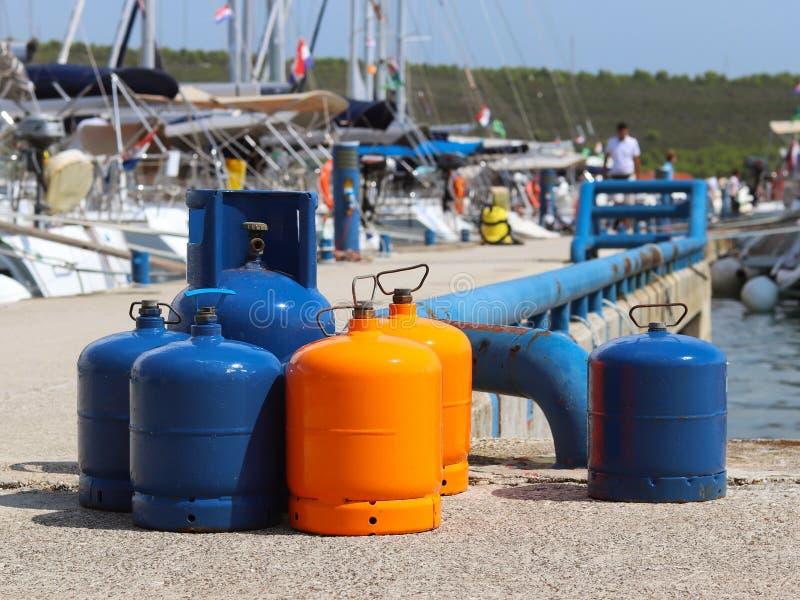 Touristische Gasflaschen stehen auf dem Pier im Jachthafen gegen den Hintergrund von Segeljachten Vorbereitungen für eine Charter stockfotos