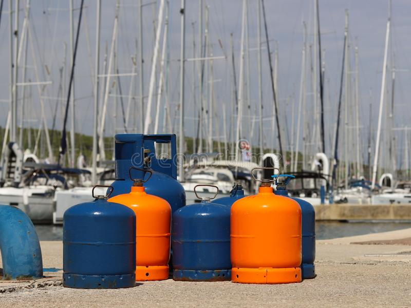 Touristische Gasflaschen stehen auf dem Pier im Jachthafen gegen den Hintergrund von Segeljachten Vorbereitungen für eine Charter lizenzfreie stockfotografie