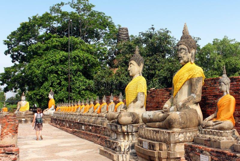 Touristische gehende aufpassende alte Buddha-Statuen an Wat Yai Chaimongkol-Tempel in Ayutthaya, Thailand lizenzfreie stockfotos
