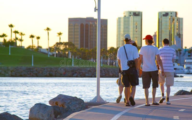 Touristische Männer, die am Strand gehen lizenzfreies stockfoto