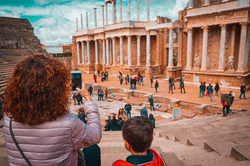 Touristische Mutter und Kind, die ein Foto in antiken Roman Theatre von Mérida, Spanien macht lizenzfreies stockfoto