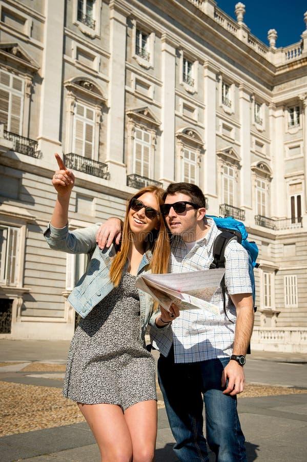 Touristische Paare der Freunde, die Madrid in die Feiertage die Stadt besichtigend glücklich mit Stadtplan besichtigen lizenzfreie stockfotos