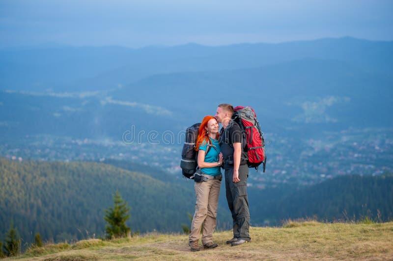 Touristische Paare mit Rucksäcken auf der Straße in den Bergen lizenzfreies stockfoto