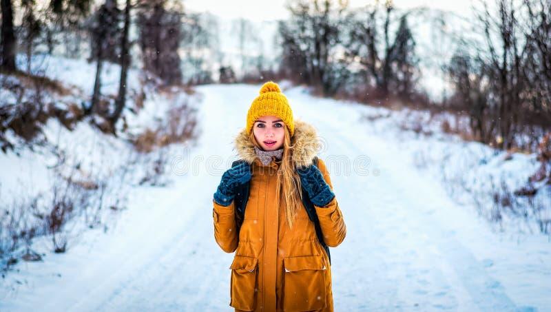 Touristische Reisendfrau ist im Winterholz auf einer schneebedeckten Straße lizenzfreie stockbilder