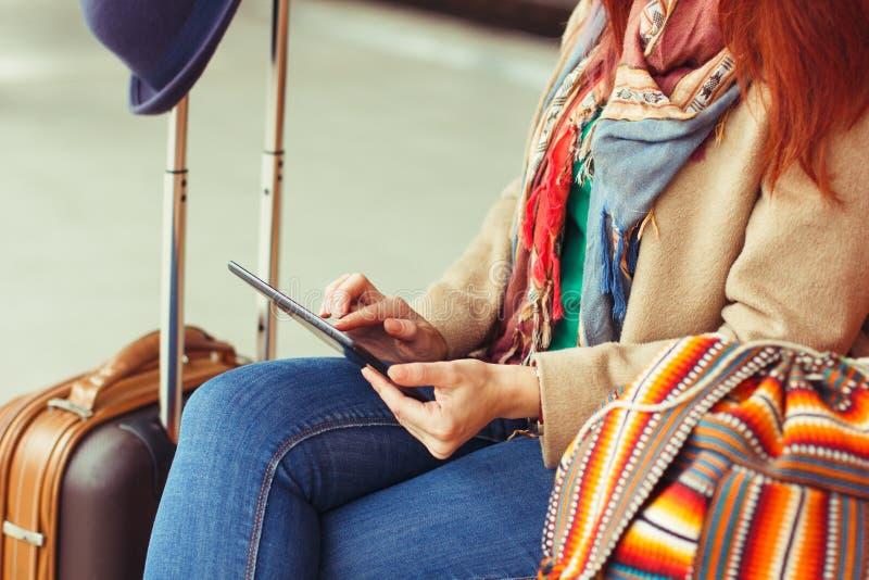 Touristische simsende Mitteilung des Hippies auf Tablette oder Technologiemodell Personenreisender, der Computer auf Bahnstation  lizenzfreie stockfotografie
