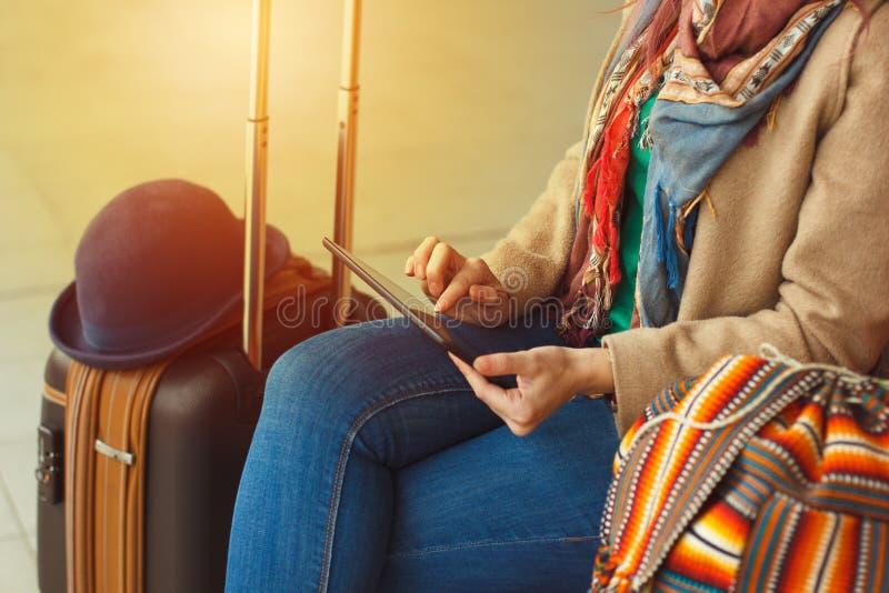 Touristische simsende Mitteilung des Hippies auf Tablette oder Technologiemodell Personenreisender, der Computer auf Bahnstation  lizenzfreies stockbild