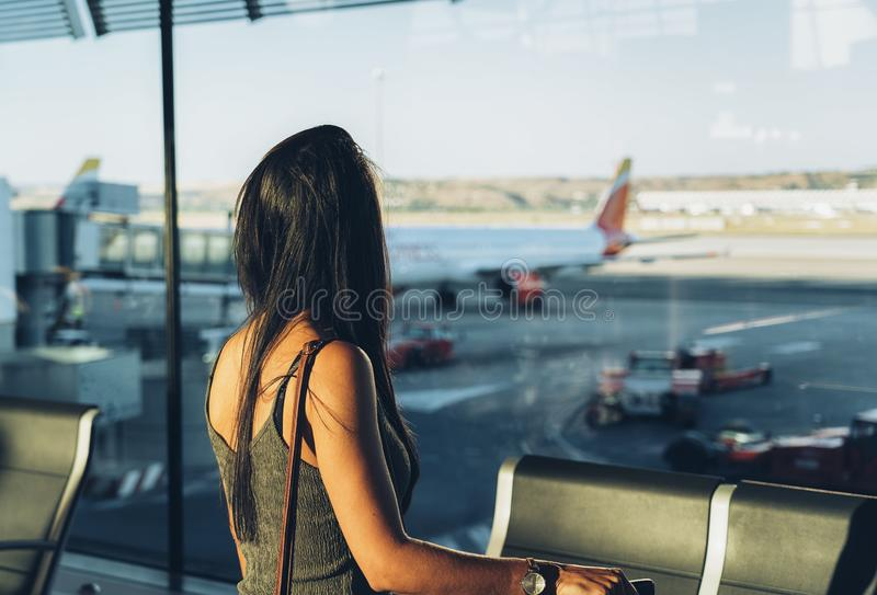 Touristische Stellung der Frau mit aufpassendem Fenster des Gepäcks am Flughafen, der seinen Flug wartet stockfoto