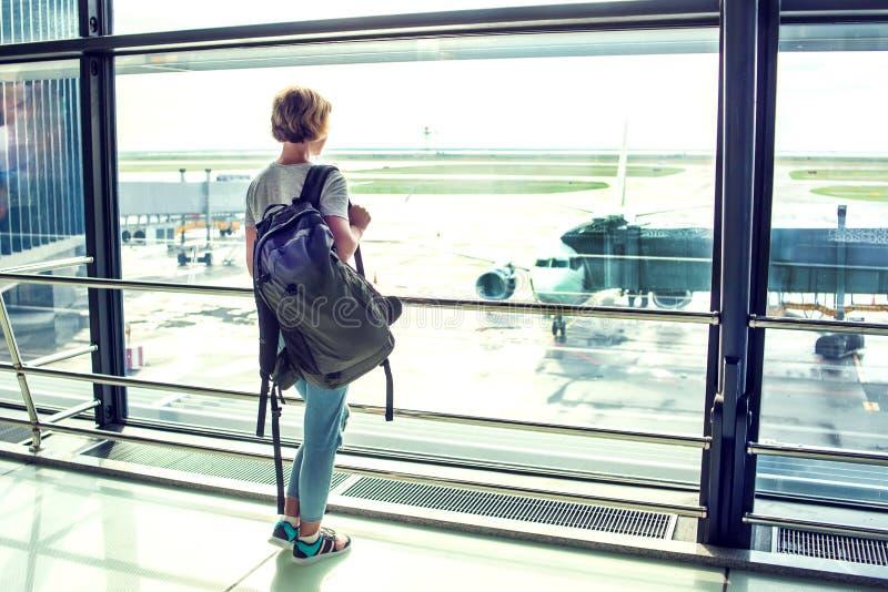 Touristische Stellung der Reise mit dem Gepäck, das am Flughafenfenster aufpasst lizenzfreie stockfotografie