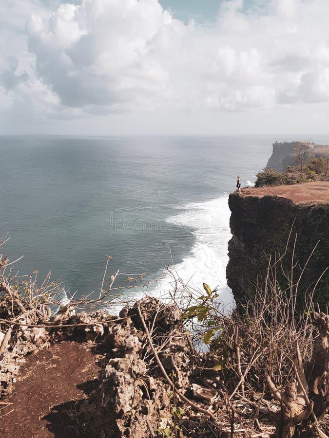 Touristische Stellung des Mädchens auf der Klippe stockfoto