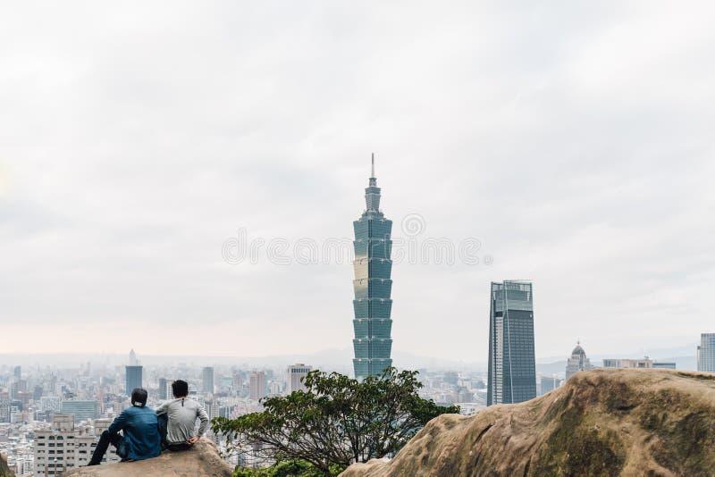 Touristische Trekkers, die auf Steinen sitzen und Wolkenkratzer Taipehs 101 vom Xiangshan-Elefant-Berg am Abend in Taipeh sehen stockfotos