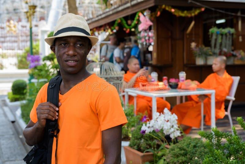 Touristischer denkender Mann des jungen Schwarzafrikaners beim Halten des Rucksacks lizenzfreie stockfotos