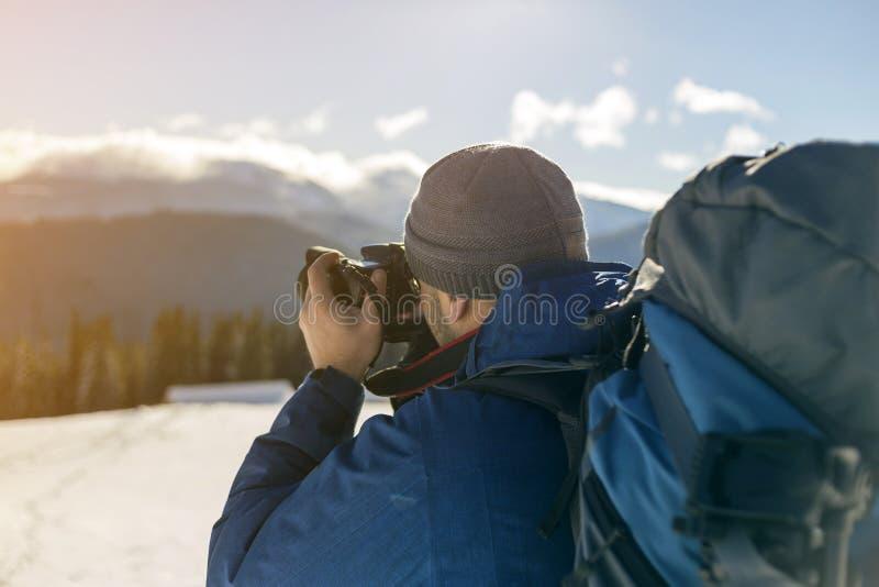 Touristischer Fotograf des Wanderermannes in der warmen Kleidung mit Rucksack und Kamera, die Foto des schneebedeckten Tales und  stockfotografie