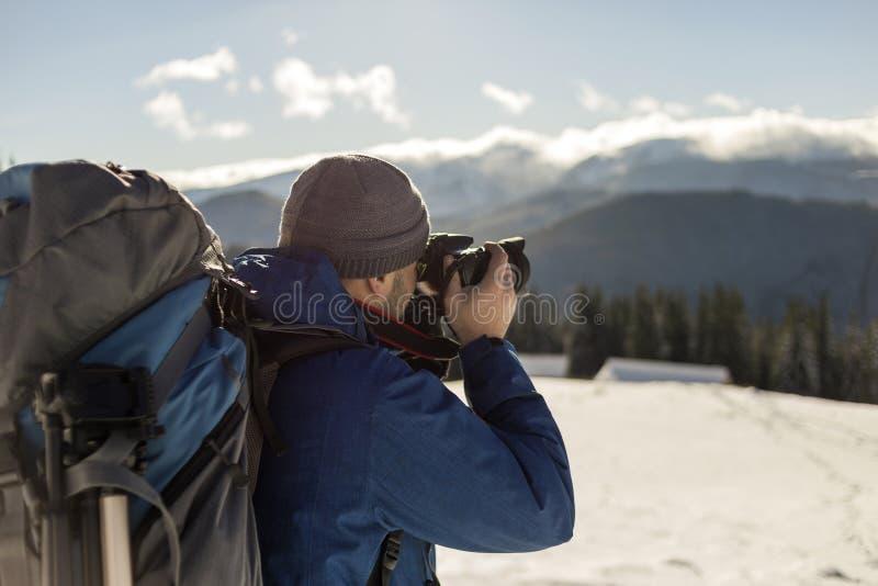 Touristischer Fotograf des Wanderermannes in der warmen Kleidung mit Rucksack und Kamera, die Foto des schneebedeckten Tales und  lizenzfreies stockbild