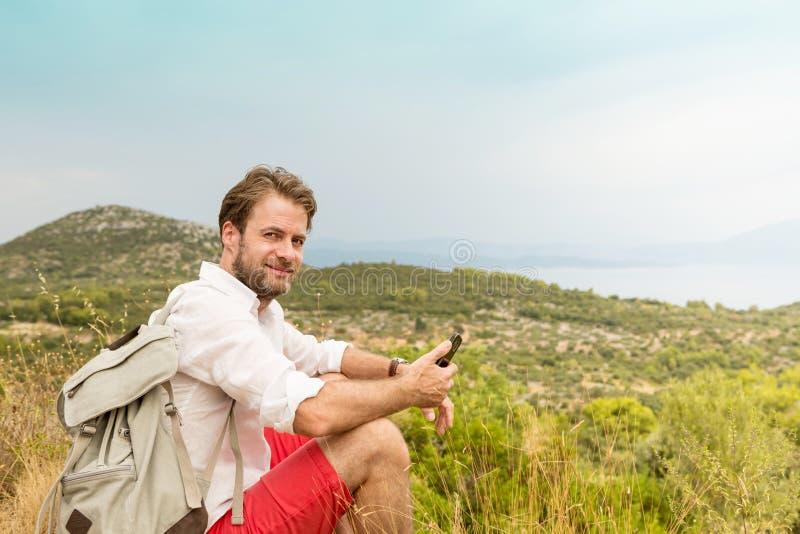 Touristischer Mann, der eine Pause während Gebirgsreise macht lizenzfreie stockfotos