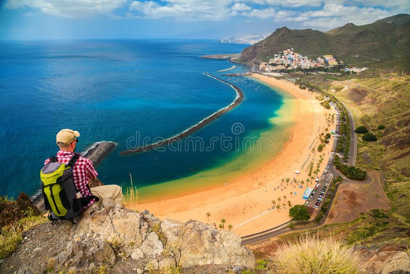 Touristischer Mann, der am Rand einer Klippe sitzt lizenzfreies stockfoto