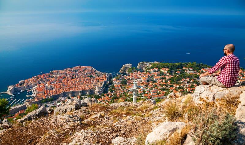 Touristischer Mann, der unten zur schönen Stadt von Dubrovnik schaut lizenzfreie stockbilder