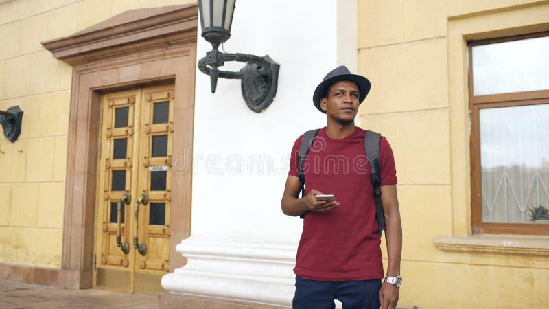 Touristischer Mann des Afroamerikaners, der Smartphoneon-line-Karte verwendet, um richtige Richtungen zu finden, an der Straße zu stockbilder