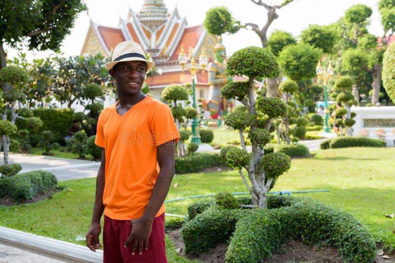 Touristischer Mann des jungen glücklichen Schwarzafrikaners, der bei Wat Arun lächelt stockfoto