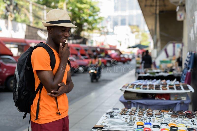 Touristischer Mann des jungen glücklichen Schwarzafrikaners, der draußen lächelt und kauft lizenzfreie stockfotos