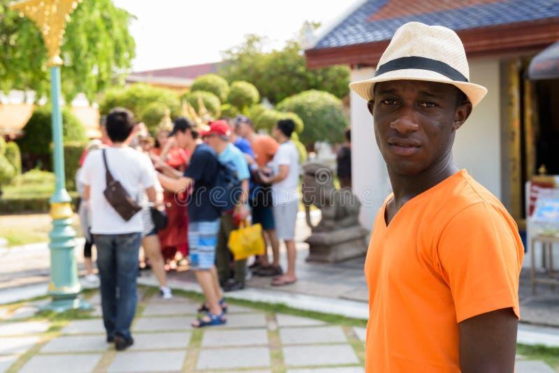 Touristischer Mann des jungen Schwarzafrikaners, der buddhistischen Tempel besucht stockfotografie