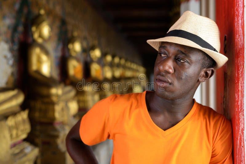Touristischer Mann des jungen Schwarzafrikaners, der am buddhistischen Tempel denkt lizenzfreies stockfoto
